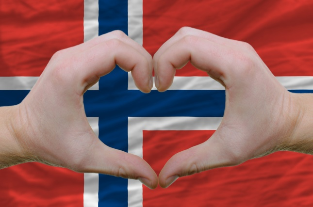 Heart and love gesture showed by hands over flag of norway backg
